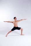 Male yoga model. A male yoga instructor in a yoga pose, wearing black shorts, and isolated on a clean backdrop Stock Images