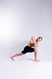 Male yoga model. A male yoga instructor in a yoga pose, wearing black shorts, and isolated on a clean backdrop Stock Photos