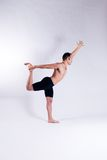 Male yoga model. A male yoga instructor in a yoga pose, wearing black shorts, and isolated on a clean backdrop Royalty Free Stock Photos