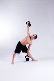 Male yoga model. A male yoga instructor in a yoga pose, wearing black shorts, and isolated on a clean backdrop Royalty Free Stock Image