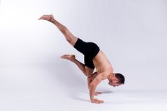 Male yoga model. A male yoga instructor in a yoga pose, wearing black shorts, and isolated on a clean backdrop Stock Image