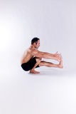 Male yoga model. A male yoga instructor in a yoga pose, wearing black shorts, and isolated on a clean backdrop Stock Photo