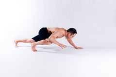Male yoga model. A male yoga instructor in a yoga pose, wearing black shorts, and isolated on a clean backdrop Royalty Free Stock Photo
