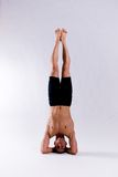 Male yoga model. A male yoga instructor in a yoga pose, wearing black shorts, and isolated on a clean backdrop Stock Photography