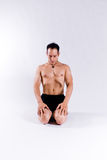 Male yoga model. A male yoga instructor in a yoga pose, wearing black shorts, and isolated on a clean backdrop Royalty Free Stock Photography
