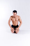 Male yoga model. A male yoga instructor in a yoga pose, wearing black shorts, and isolated on a clean backdrop Royalty Free Stock Images