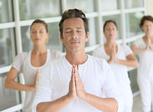 Male yoga teacher giving yoga course. Mature men amongst group doing yoga exercises Stock Photography
