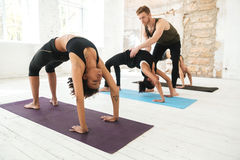 Male yoga trainer helping a woman to do yoga stretches Royalty Free Stock Images
