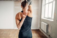 Male yoga on training, flexibility of human body. Balance exercise on mat in gym with grunge interior. Fit workout indoors Stock Photography