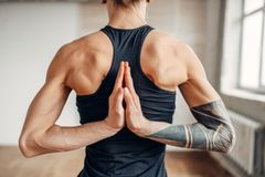 Male yoga on training, flexibility of human body. Balance exercise on mat in gym with grunge interior. Fit workout indoors Royalty Free Stock Photography