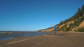 Strong man practicing difficult yoga pose on the beach stock footage