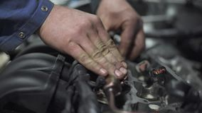 Male young auto specialist taking and repairing parts in the gearbox of the car in planning car inspection. Young male auto specialist taking and repairing parts stock footage