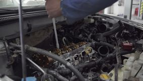 Male young auto specialist tightens the bolts with a screwdriver in the gearbox of the car in planning car inspection. Young male auto specialist tightens the stock video