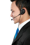 Male young call center. Side view portrait of young call center speaking over headset Royalty Free Stock Photos