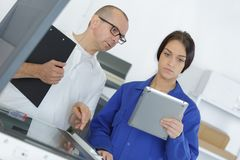 Male and young female workers discussing with tablet Stock Photography