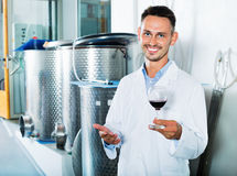 Male young winemaker in lab coat having glass of wine. Smiling male young winemaker in lab coat having glass of wine in hands Stock Photo