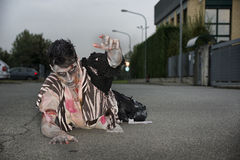 Male zombie crawling on his knees, on empty city street Royalty Free Stock Photos