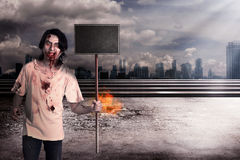 Male zombie holding wooden board over city on fire. You can put your message on the board Stock Image