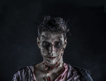Male zombie standing on black blackground Royalty Free Stock Images