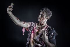Male zombie using cell phone to take selfie, standing. Male zombie using cell phone to take selfie photo, standing on black smoky background, half body shot Stock Photos