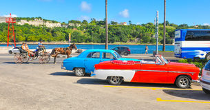 Malecon Avenue, Havana. Havana, Cuba - December 19, 2016: Tourists and vintage cars on the Malecon, major avenue and landmark in Havana, Cuba Royalty Free Stock Image