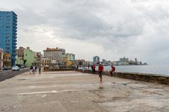HAVANA, CUBA - OCTOBER 21, 2017: Malecon Avenue in Havana, Cuba. People walking and fishing in Caribbean Sea. Malecon Avenue in Havana, Cuba. People walking and Stock Photos
