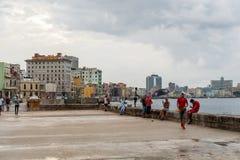 HAVANA, CUBA - OCTOBER 21, 2017: Malecon Avenue in Havana, Cuba. People walking and fishing in Caribbean Sea. Malecon Avenue in Havana, Cuba. People walking and Stock Photography