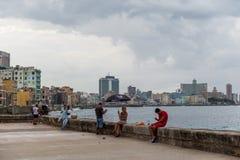 HAVANA, CUBA - OCTOBER 21, 2017: Malecon Avenue in Havana, Cuba. People walking and fishing in Caribbean Sea. Havana Cityscape in. Malecon Avenue in Havana, Cuba Royalty Free Stock Photo