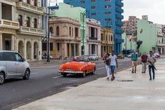 HAVANA, CUBA - OCTOBER 21, 2017: Malecon Avenue in Havana, Cuba. People walking, Old Cars in Background. Malecon Avenue in Havana, Cuba. People walking, Old Cars Stock Photo