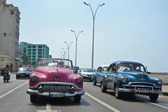 Malecon Classic Cars. Havana - July 18: American classic cars driving along the famous Malecon coast road in Havana, Cuba on July 18, 2014. Classic car rides are Stock Photography