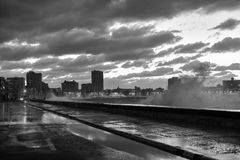 Malecon - Havana, Cuba. Evening at the seaside drive Malecon in Havana, Cuba as the waves crash over Royalty Free Stock Image