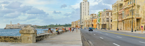 The Malecon in Havana with people and traffic. HAVANA,CUBA - MAY 3:2015 : The Malecon seawall in Havana with a view of old buildings, people and old cars Stock Images