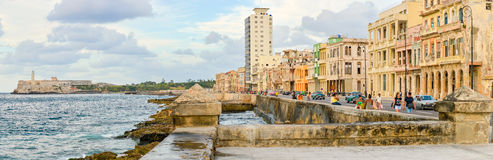 The Malecon in Havana with people and traffic. The Malecon seawall in Havana with a view of old buildings, people and old cars Royalty Free Stock Image