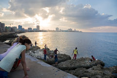 Malecon at sunset. The Malecon of Havana at sunset with Cubans fishing and girls watching, Cuba Royalty Free Stock Photo