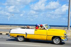 Malecon in Havana with typical American car, Cuba. Malecon in Havana and typical American car with tourists, Cuba Royalty Free Stock Image