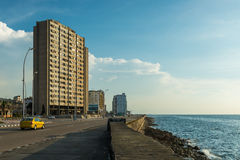 The Malecon. The old architecture of Havana, Cuba, stands across from the Malecon, a long boardwalk that runs along the Caribbean sea Stock Photo