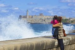Malecon promenade and a couple in Havana, Cuba, Caribbean. Mum and daughter watching waves in Malecon promenade in Havana, Cuba Stock Image