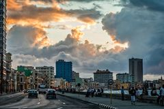 Malecon promenade street with walking people and road with traff. Ic in the evening time with sunset clouds, Havana, Cuba Stock Photo