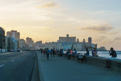 Malecon view, people and buildings in sunset. La Havana, Cuba December 25, 2016 Malecon typical view in sunset with La Havana buildings at background Royalty Free Stock Images
