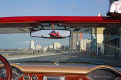 Malecon vintage. HAVANA - January 29: driving along the famous Malecon in a 1950s chevrolet in Havana, Cuba on January 29, 2009. A trip in a classic car is an Stock Images