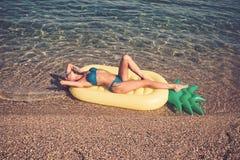 Malediven- oder Miami- Beachwasser Mädchen, das auf Strand mit Luftmatraze ein Sonnenbad nimmt Sommerferien und -reise zum Ozean lizenzfreie stockfotos