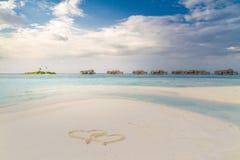 Malediven-Paradiesstrand- und -herzformen, die in Sand zeichnen Schwermütige Landschaft und Meer auf Himmel für Feiertagsferien-H lizenzfreie stockbilder
