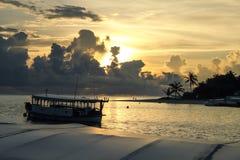 Maledivische Boote und Urlaubsinsel im goldenen tropischen Sonnenuntergang stockfoto
