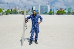 Maledivischer Polizeibeamte mit Schild und Taktstock Stockfotos