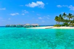 Maledivisches Wasserlandhaus und blaues Meer Stockfotografie