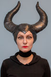 Maleficent  - beautiful woman from a fairytale with hair horns and creative make-up for the Halloween party.  Stock Image