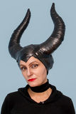 Maleficent  - beautiful woman from a fairytale with hair horns and creative make-up for the Halloween party.  Royalty Free Stock Photo