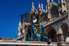 Maleficent in Venice. Maleficent or Grimilde mask during Venice Carnival with Saint Mark Basilica Royalty Free Stock Photography