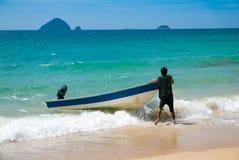 Maleise strand en mens die met zijn boot worstelen stock afbeeldingen