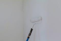 Malen einer rauen Wand durch Malereirolle und weißen Latex Dieses Archivbild enthält eine Farbenrolle Lizenzfreie Stockfotografie